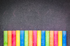 Row of rainbow chalk on blackboard Stock Photography