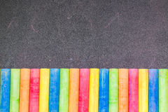 Row of rainbow chalk on blackboard Royalty Free Stock Image