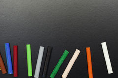 Row of rainbow colored chalk on  blackboard background. Row of rainbow colored chalk on  blackboard background Royalty Free Stock Images