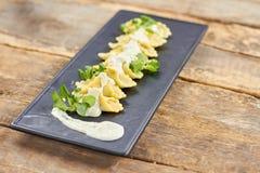 Row of ravioli on black rectangle plate. Decorated ravioli dish Stock Photography