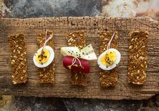 Row of raw bread with sunflower seeds, carrots, sesame, flax see. D and other vegetables. Egg halves, microgreen, cucumber and beetroot slices on old wooden Royalty Free Stock Photos