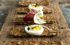 Row of raw bread with sunflower seeds, carrots, sesame, flax see. D and other vegetables. Egg halves, microgreen, cucumber and beetroot slices on old wooden Stock Photography