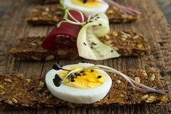 Row of raw bread with sunflower seeds, carrots, sesame, flax see. D and other vegetables. Egg halves, microgreen, cucumber and beetroot slices on old wooden Stock Images