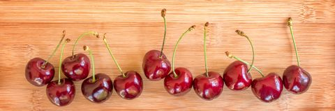 Row of real cherries on wood background Stock Photos