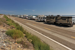 Row of recreational vehicles parked on road Stock Images