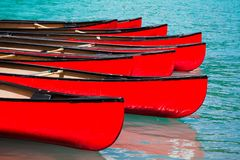 Row of red canoes in lake. Calm water stock photos