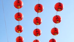 Row of red Chinese paper lanterns with ornate gold patterns and tassels. hanging on wires outside. Shot on the sky background at B. Row of red Chinese paper stock video footage