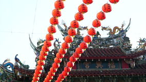 Row of red Chinese paper lanterns with ornate gold patterns and tassels. hanging on wires outside. Shot on the sky background at B. Row of red Chinese paper stock footage