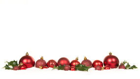 Row of red christmas ball decorations and green holly ilex in the snow. On a white background Royalty Free Stock Photo