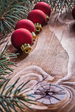 Row of red christmas baubles branches of fir tree on old wooden Stock Photography