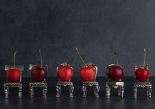 Row of red delicious cherries placed on vintage silver chairs on Stock Photos