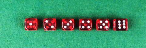 A row of red dices from one to six. On green background royalty free stock images