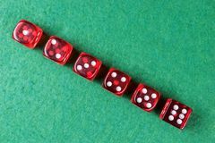 A row of red dices from one to six. On green background stock photos