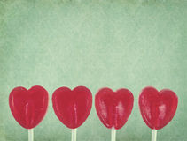 Row of red lollipop hearts on vintage background Royalty Free Stock Photo