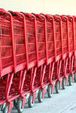 Row of red metal shopping carts Royalty Free Stock Photography