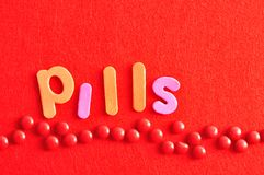 A row of red pills with the word pills. A row of red pills on a red background with the word pills Stock Image
