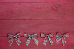 Row of red plaid Christmas bows border antique red wooden background Stock Images