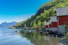 A row of red small houses with small boats at Flam village Royalty Free Stock Photography