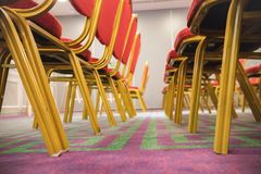 Row of red soft chairs in a conference room with a carpet. The frame goes into perspective. Bottom view Stock Photos