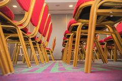 Row of red soft chairs in a conference room with a carpet. The frame goes into perspective. Bottom view Royalty Free Stock Photography