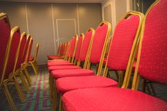Row of red soft chairs in a conference room with a carpet. The frame goes into perspective Royalty Free Stock Photo