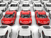 Row of red sports cars standing out of the lot of white cars Stock Photos