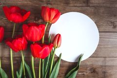Row of red tulips on wooden background with space for message. Women`s or Mother`s Day background. Top view. Row of red tulips on wooden background with space Stock Photo