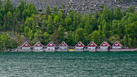 Row of red vacation houses in the fjord Stock Photos