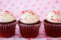 Row of red velvet cupcakes with red sprinkles stock images