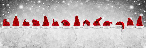 Row of red white santa claus christmas xmas hat on empty concret Royalty Free Stock Image