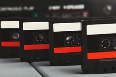 Row of vintage audio cassettes and tape recorder at gray background Royalty Free Stock Photography