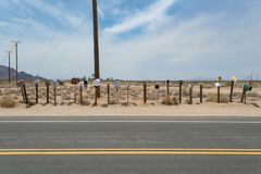 Row of roadside mail boxes in the Mojave desert. Power lines royalty free stock image