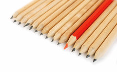 A row of rough graphite pencils with color red one Stock Image