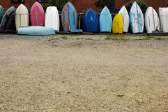 Row of rowing boats. A row of colorful small boats lean against a fence with a gravel yard in front Royalty Free Stock Photo