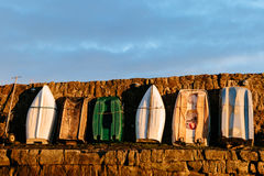A row of rowing boats standing upright on land. 6 rowing boats standing upright facing a stone wall on a pier royalty free stock images