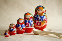 Row Russian Matryoshkas and two wooden spoons.  Royalty Free Stock Image