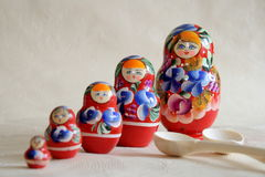 Row Russian Matryoshkas and two wooden spoons Stock Images
