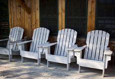 White Adirondack Chairs in a Row. A row of rustic Adirondack chairs on a porch of a wooden lodge Stock Photos