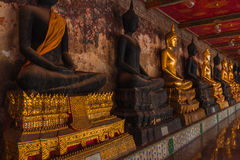 Row of Sacred Buddha images. Golden Buddha and Thai architecture in Wat Suthat in Bangkok, Thailand stock image