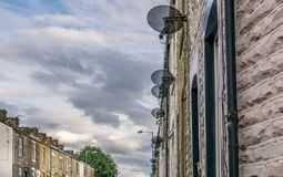 A row of a satellite dishes on terraced houses royalty free stock images