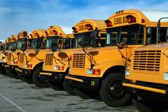 Row of school buses. A long row of parked public school buses stock images