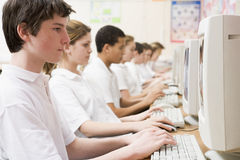Row of schoolchildren studying on computer stock image