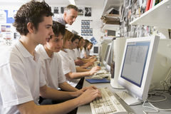 Row of schoolchildren studying on computer stock photography