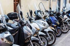 Row of scooters parked roadside Royalty Free Stock Image