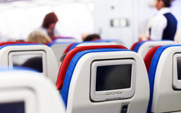 Row of seats with monitors inside of aircraft. Row of seats with lcd monitors inside of aircraft stock photography