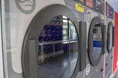 Row of self-service washing machines doors. Washing machines in the self service laundry stock photo