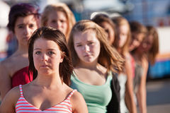 Row of Serious Teen Women. Row of serious teenage girls at an amusement park Royalty Free Stock Images