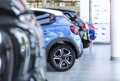 Row of shiny cars for sale parked in a showroom interior royalty free stock images