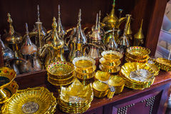 Row of shiny traditional coffee pots and lamp Royalty Free Stock Photography