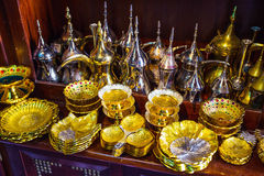 Row of shiny traditional coffee pots and lamp Royalty Free Stock Image